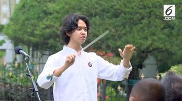 Tristan memimpin para hadirin saat menyanyikan lagu Indonesia Raya.