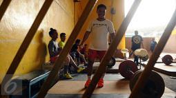 Lifter Indonesia, Eko Yuli Irawan bersiap melakukan angkatan saat latihan di luar gedung PB PABBSI, Stadion GBK Jakarta, Senin (11/1/2016). Latihan dilakukan diluar gedung akibat proses renovasi gedung PB PABBSI. (Liputan6.com/Helmi Fithriansyah)