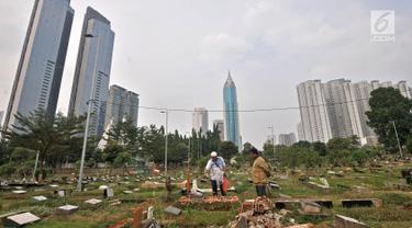 Warga berziarah di salah satu makam di TPU Karet Bivak, Jakarta, Kamis (12/7). Jakarta diprediksi mengalami krisis lahan makam 1,5 tahun lagi atau pada 2019 mendatang. (Merdeka.com/Iqbal Nugroho)