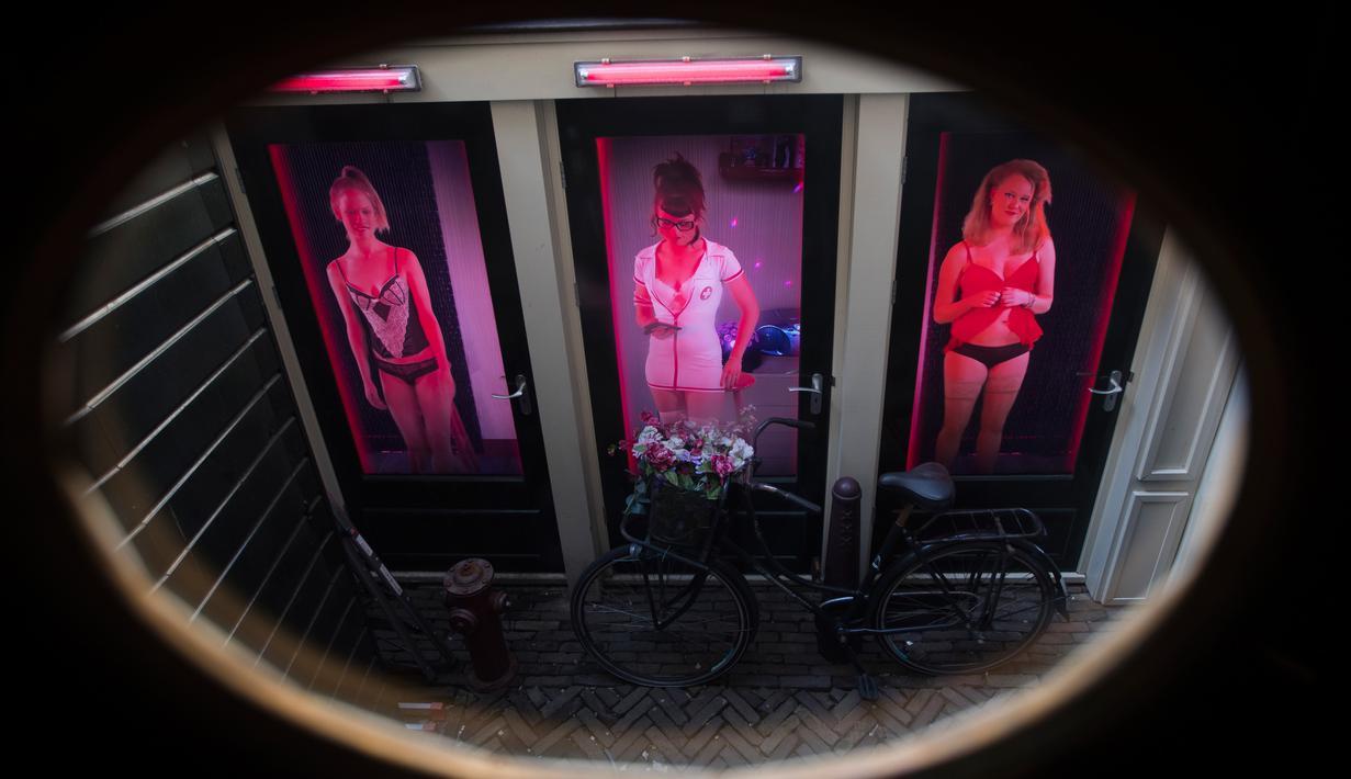 Gambar tiga perempuan pekerja seks terlihat di tiga pintu di Red Light Secrets Museum of Prostitution, Amsterdam Belanda (1/4). Pemerintah Amsterdam mengumumkan bakal segera mengakhiri tur wisata ke Red Light District. (AP Photo/Peter Dejong)