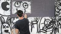 Siswa sedang melukis mural di dinding sekolah JIS, Jakarta, Sabtu (7/4). Siswa juga dapat memahami cara pandang dan mempelajari bagaimana proses seorang seniman yang konsisten fokus menghasilkan sebuah karya seni visual art. (Liputan6.com/Herman Zakharia)