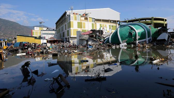 Orang-orang memeriksa kerusakan sebuah pusat perbelanjaan setelah gempa bumi dan tsunami menghantam Kota Palu di Sulawesi Tengah, Minggu (30/9). Dampak dari bencana tersebut melulunlantakkan bangunan dan ratusan jiwa meninggal dunia. (AP/Tatan Syuflana)