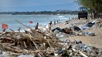 Pekerja menggunakan alat berat membersihkan sampah dan sampah plastik saat pembersihan pantai Kuta dekat Denpasar di pulau wisata Bali (6/1/2021). (AFP/Sonny Tumbelaka)