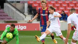 Gelandang Real Madrid, Luka Modric, berusaha mencetak gol ke gawang Barcelona pada laga lanjutan Liga Spanyol di Camp Nou Stadion, Sabtu (24/10/2020) malam WIB. Real Madrid menang 3-1 atas Barcelona. (AFP/Lluis Gene)
