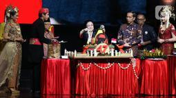 Ketua Umum PDI Perjuangan Megawati Soekarnoputri (tengah) memotong tumpeng disaksikan Presiden Joko Widodo (ketiga kanan) dan Wakil Presiden Ma'ruf Amin (ketiga kiri) saat pembukaan Rakernas I dan HUT ke-47 PDIP di JIEXPO Kemayoran, Jakarta, Jumat (10/1/2020). (Liputan6.com/Johan Tallo)