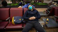 Pelancong memakai masker saat tidur siang di Bandara Internasional Ibu Kota Beijing, 23 Januari 2020. China pada Kamis (23/1) menutup sebuah kota berpenduduk lebih dari 11 juta orang dalam upaya memerangi wabah virus corona, tindakan yang belum pernah terjadi sebelumnya.  (AP/Mark Schiefelbein)