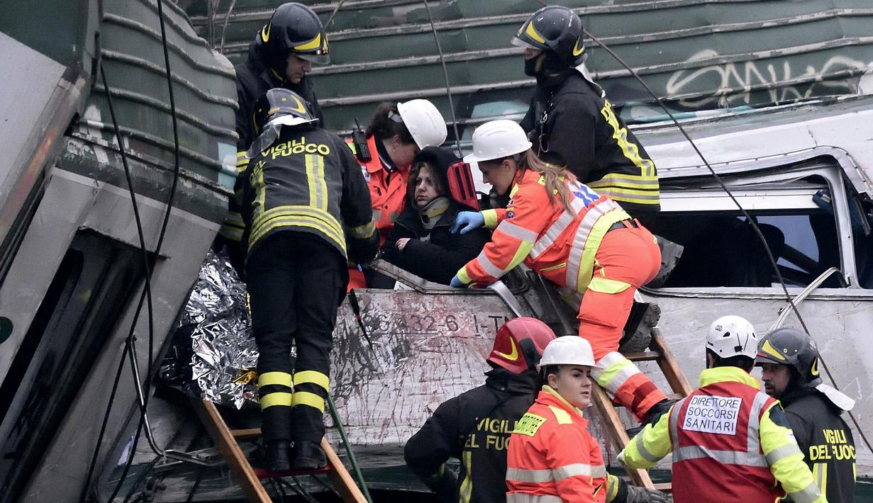 Tim penyelamat membantu seorang penumpang keluar dari sebuah kereta yang tergelincir di Stasiun Pioltello Limito, Milan, Italia, Kamis (25/1). Tiga penumpang tewas dan 10 lainnya luka serius. (Flavio Loscalzo/ANSA via AP)