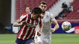 Bek Atletico Madrid, Stefan Savic (kiri) berebut bola dengan striker SD Huesca, Rafa Mir dalam laga lanjutan Liga Spanyol 2020/2021 pekan ke-32 di Wanda Metropolitano Stadium, Madrid, Kamis (22/4/2021). Atletico menang 2-0 atas SD Huesca. (AFP/Javier Soriano)