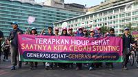 Peserta kampanye cegah stunting membawa spanduk saat berjalan di kawasan Bundaran Hotel Indonesia, Jakarta, Minggu (16/9). Peserta juga bakal memberikan penyuluhan tentang stunting ke masyarakat sekitar. (Liputan6.com/Helmi Fithriansyah)