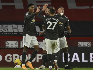 Penyerang Manchester United, Marcus Rashford (kiri) berselebrasi dengan rekannya usai mencetak gol ke gawang Sheffield United pada pertandingan Liga Inggris di stadion Bramall Lane di Sheffield, Inggris, Jumat (18/12/2020). Rashford mencetak dua gol dan mengantar MU menang 3-2. (AP Photo/Rui Vieira)