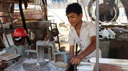 """Seorang anak bekerja di sebuah lokakarya di distrik Abs utara, Yaman, (8/5). Perwakilan UNICEF di Yaman, Meritxell Relano mengatakan generasi anak-anak di Yaman menghadapi masa depan yang suram karena tidak ada akses ke pendidikan."""" (AFP Photo/Essa Ahmed)"""