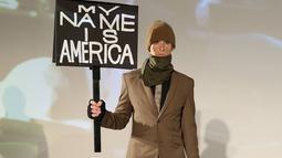 Seorang model membawa poster saat presentasi karya desainer Robert James dalam New York Fashion Week (NYFW) di New York,AS  (30/1). (Robin Marchant Getty Images/AFP)