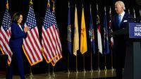 Calon Presiden Partai Demokrat, Joe Biden memperkenalkan pasangannya, Kamala Harris untuk berbicara selama acara kampanye di Alexis Dupont High School di Wilmington, Rabu (12/8/2020). Keduanya tampil perdana di depan publik sebagai pasangan capres-cawapres. (AP Photo/Carolyn Kaster)