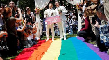 Pasangan sesama jenis berjalan di atas bendera pelangi raksasa saat melangsungkan pesta pernikahan mereka di Taipei, Taiwan, Jumat (24/5/2019). Taiwan menggelar pernikahan sesama jenis pertama di Asia. (REUTERS/Tyrone Siu)
