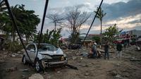 Orang-orang melihat kerusakan pantai yang terkena tsunami setelah gempa kuat disusul tsunami menghantam Kota Palu di Sulawesi Tengah, Sabtu (29/9). Dampak dari bencana tersebut melulunlantakkan bangunan dan ratusan jiwa meninggal dunia. (AFP/Bay ISMOYO)