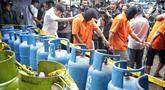 Tersangka penyuntikan tabung gas di Cipayung, Jakarta, Selasa (22/1). Polda Metro Jaya menyita 1.200 tabung LPG ukuran 3 Kg, 242 ukuran 12 Kg, 14 selang pipa besi regulator pemindah isi gas dan 1 kantong segel tabung gas. (Liputan6.com/Faizal Fanani)