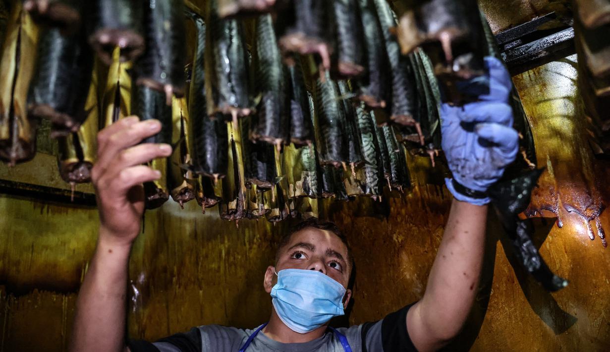Seorang pemuda Palestina mengasapi makarel untuk dijual di pasar ikan menjelang liburan Idul Fitri di kota Rafah di Jalur Gaza selatan (3/5/2021). Ikan asap makarel menjadi salah satu menu hidangan buka puasa terfavorit bagi warga Gaza selama Ramadhan. (AFP/Said Khatib)
