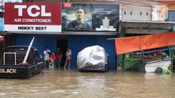 Aktivitas karyawan pertokoan di Jalan KH Hasyim Ashari, Ciledug, Tangerang, Kamis (2/1/2020). Banjir yang melanda Ciledug dan sekitarnya membuat aktivitas perekonomian di kawasan tersebut lumpuh sementara. (Liputan6.com/Angga Yuniar)