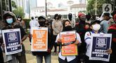 Sejumlah buruh saat melakukan aksi di depan Balai Kota DKI Jakarta, Selasa (26/10/2021). Pada aksi tersebut massa buruh menuntut kenaikan UMP 2022 sebesar 10 persen, berlakukan UMSK 2021 dan mencabut UU Omnibus Law. (Liputan6.com/Faizal Fanani)