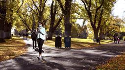 Seorang wanita berjalan sambil bermain ponsel di taman kota di Melbourne, Australia (3/6/2021). Pihak berwenang mengumumkan Lockdown di Melbourne diperpanjang tujuh hari lagi ketika negara itu berusaha untuk membasmi sekelompok kasus Covid-19 di Melbourne. (AFP Photo/William West)