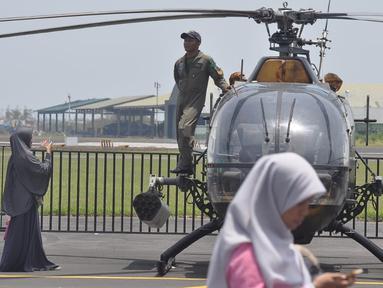 Seorang prajurit  berdiri di sebuah helikopter milik TNI AD ada pameran alat utama sistem persenjataan (Alutsista) di Lanumad  Ahmad Yani Semarang, Jumat (5/10). Pameran alutsista tersebut dalam rangka memeriahkan HUT Ke-73 TNI. (Liputan6.com/Gholib)