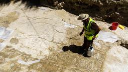 Seorang Arkeolog membersihkan pasir-pasir yang menutupi mosaik menggunakan air di Larnaca, Siprus (14/7).Mereka percaya bahwa mosaik ini merupakan peninggalan Romawi dari Kerajaan Kition. (Iakovos Hatzistavrou / AFP)