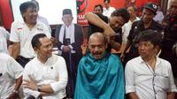 Wali Kota Solo fx Hadi Rudyatmo melakukan aksi gundul sebagai wujud syukur atas kemenangan Jokowi-Ma'ruf Amin dalam perhitungan quick count, Rabu malam (17/4).(Liputan6.com/Fajar Abrori)