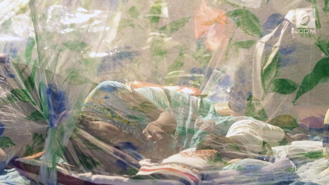 Pencari suaka menidurkan anaknya di dalam tenda yang dibangun di atas trotoar depan kantor UNHCR, Jalan Kebon Sirih, Jakarta, Jumat (5/7/2019). Para pencari suaka dari sejumlah negara berkonflik berharap UNHCR bisa segera memberikan jaminan perlindungan bagi mereka. (Liputan6.com/Helmi Fithriansyah)