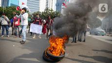 Massa Himpunan Mahasiswa Islam (HMI) membakar ban bekas saat berunjuk rasa menentang UU Cipta Kerja di kawasan Patung Kuda, Jakarta, Rabu (28/10/2020). Massa meminta Presiden Joko Widodo segera mencabut UU Cipta Kerja melalui Peraturan Pemerintah Pengganti Undang-Undang. (Liputan6.com/Faizal Fanani)