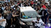 Para penggemar berkerumun di samping mobil jenazah yang membawa mendiang legenda sepak bola Argentina, Diego Maradona menuju pemakaman, di Buenos Aires, Kamis (26/11/2020).  Maradona meninggal dunia dalam usia 60 tahun pada Rabu (25/11) karena serangan jantung. (Raul FERRARI/TELAM/AFP)