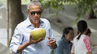 Barack Obama saat menikmati air kelapa di sepanjang Sungai Mekong di Luang Prabang, Laos (7/9). Obama menjadi presiden AS pertama yang mengunjungi Laos dan mendarat di Vientiane akhir pada 5 September. (AFP PHOTO/SAUL Loeb)
