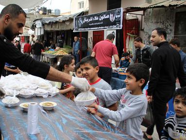 Para pekerja Palestina membagikan makanan gratis pada hari keempat Ramadan di Deir al-Balah, Jalur Gaza tengah, pada 27 April 2020. (Xinhua/Rizek Abdeljawad)