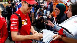 Pembalap Ferrari Sebastian Vettel menandatangani tanda tangan untuk para penggemar saat tiba di Sirkuit Melbourne Grand Prix di Melbourne, Jumat (15/3). GP Australia digelar di Sirkuit Melbourne Grand Prix, 15 hingga 17 Maret. (Reuters/Edgar Su)
