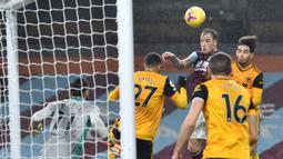 Striker Burnley, Ashley barnes (tengah), menyundul bola yang menghasilkan gol pertama timnya ke gawang Wolverhampton Wanderers dalam laga lanjutan Liga Inggris pekan ke-14 di Turf Moor Stadium, Senin (21/12/2020). Burnley menang 2-1 atas Wolverhampton. (AFP/Peter Powell/Pool)