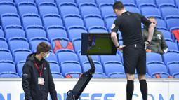 Wasit Chris Kavanagh melihat layar VAR saat Manchester United melawan Brighton Hove Albion pada laga Liga Inggris, Sabtu (26/9/2020). Setan Merah menang dengan skor 3-2. (Glyn Kirk/Pool via AP)