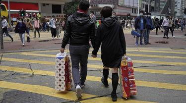 Sepasang suami istri membawa persediaan tisu toilet di sebuah jalan pada Hari Valentine di Hong Kong, Jumat, (14/2/2020). Hari Valentine pada tanggal 14 Februari adalah sebuah hari di mana para kekasih dan mereka yang sedang jatuh cinta menyatakan cintanya. (AP Photo/Kin Cheung)