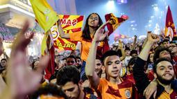 Suporter Galatasaray merayakan kemenangan timnya meraih gelar Liga Turki usai pertandingan melawan Istanbul Basaksehir di Turk Telekom Arena di Istanbul (19/5/2019). Galatasaray memastikan gelar liga Turki ke-22 usai mengalahkan Istanbul Basaksehir 2-1. (AFP Photo/Yasin Akgul)