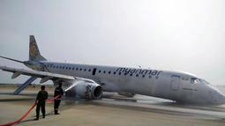 Petugas pemadam kebakaran menyemprotkan air ke pesawat Myanmar National Airline (MNA) yang mendarat tanpa roda depan di Bandara Internasional Mandalay, Myanmar, Minggu 12 Mei 2019. Kejadian ini tidak menyebabkan 82 penumpang serta tujuh kru terluka. (Aung Thura via AP)