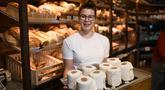 Andrea Schulz menyajikan kue berbentuk tisu toilet di toko roti Schuerener Backparadies di Dortmund, Jerman, 26 Maret 2020. Kelangkaan kertas tisu toilet memunculkan ide bagi pemilik toko roti itu, Tim Kortuem, membuat kue menyerupai barang yang diburu warga di tengah Covid-19. (Ina FASSBENDER/AFP)