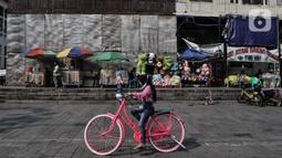 Wisatawan menaiki sepeda di kawasan wisata Kota Tua, Jakarta, Minggu (28/6/2020). Para pedagang, delman, dan jasa penyewaan sepeda pun terlihat kembali meramaikan suasana di sekitar Kali Besar. (merdeka.com/Iqbal S. Nugroho)