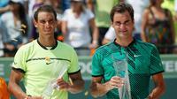 Roger Federer (kanan) dan Rafael Nadal berpose dengan trofinya di Crandon Park, Florida (2/4). Bagi Federer, ini adalah titel ketiganya di Miami atau yang pertama dalam 11 tahun usai memenanginya di 2005 dan 2006. (AP Photo/Wilfredo Lee)