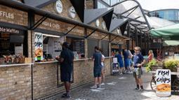 Orang-orang mengantre untuk membeli makanan di Pasar Camden di London, Inggris, pada 2 Juni 2020. Bisnis retail di ruangan terbuka dan ruang pamer mobil kembali dibuka mulai 1 Juni, sementara bisnis retail nonesensial lainnya akan dibuka pada 15 Juni. (Xinhua/Ray Tang)