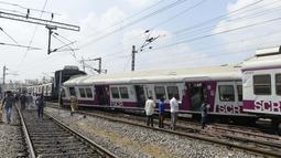 Sejumlah penumpang berdiri di samping gerbong kereta surburban yang bertabrakan dengan kereta ekspres antarkota di Stasiun Kereta Api Kachiguda di Hyderabad, India (11/9/2019). Sekitar 12 orang terluka akibat kecelakaan tersebut. (AFP Photo/Noah Seelam)