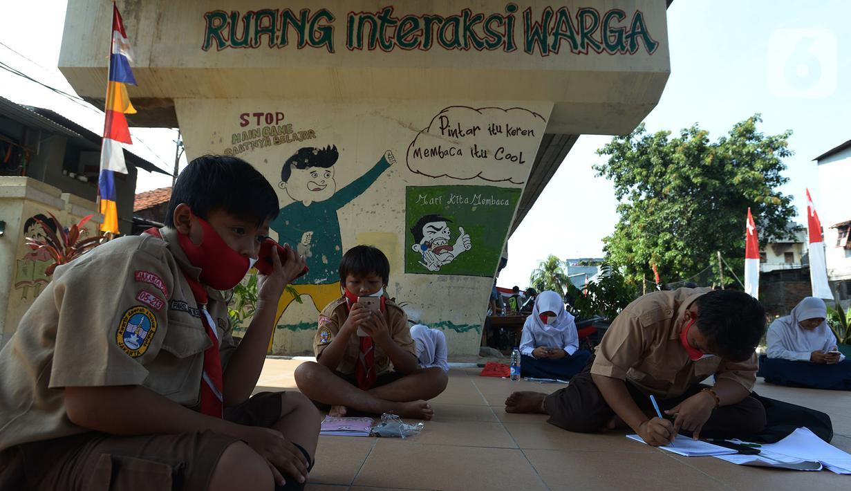 Para siswa belajar di kolong rel kereta api Mangga Besar, Jakarta,Rabu (19/8/2020). Proses belajar siswa tersebut menggunakan modem paket internet wifi gratis yang disediakan untuk mengikuti pembelajaran jarak jauh. (merdeka.com/Imam Buhori)