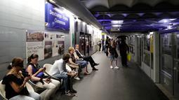 """Para komuter duduk dekat tanda yang bertuliskan """"Deschamps - Elysees Clemenceau"""" di stasiun metro Champs - Elysees Clemenceau, Paris, Senin (16/7). Hal itu untuk merayakan kesuksesan timnas Prancis menjadi juara Piala Dunia. (AFP/Thomas SAMSON)"""