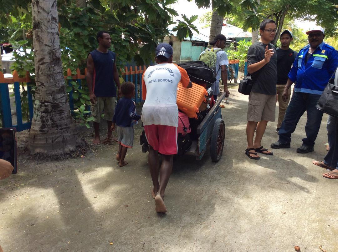 Warga Arborek mendorong gerobak berisi kopor-kopor wisatawan. (foto : Liputan6.com / katarina djanur)