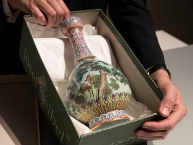 Sebuah vas China antik yang diyakini berasal dari masa Dinasti Qing pada abad ke-18 diperlihatkan di rumah lelang Sotheby, Paris, Selasa (22/5). Vas China antik berusia ratusan tahun akan dilelang di Prancis pada bulan depan. (AFP/Thomas SAMSON)