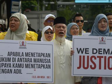Massa mengatasnamakan Alumni Universitas Indonesia membawa poster saat mengawal sidang perdana sengketa Pilpres 2019 di gedung Mahkamah Konstitusi (MK), Jumat (14/6/2019). Massa menggunakan rompi kuning dan membawa beberapa atribut, diantaranya spanduk dan beberapa banner. (merdeka.com/Imam Buhori)