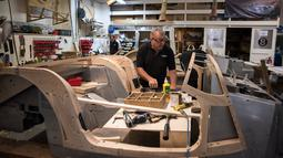 Seorang pekerja menyelesaikan pembuatan mobil klasik dengan bahan dasar kayu ash di pabrik mobil Morgan Motor Company di Malvern, Birmingham, Inggris (13/8/2019). Morgan Motor Company telah memproduksi kendaraan klasik Inggris selama lebih dari 105 tahun. (AFP Photo/Oli Scarff)