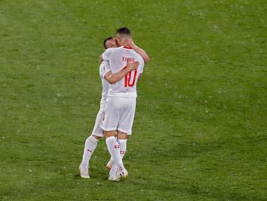 Pemain Swiss,  Xherdan Shaqiri dan Granit Xhaka merayakan kemenangan atas Serbia pada laga grup E Piala Dunia 2018 di Stadion Kaliningrad, Jumat (22/6). Selebrasi Xhaka dan Shaqiri memicu kontroversi ketika mengalahkan Serbia 2-1. (AP/Antonio Calanni)